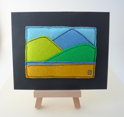 Felt applique showing three mountains in purple, acid green and grass green with a lake and foreground. ACEO size mounted on black mount board.