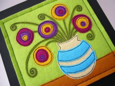 A folk art style picture showing five naif blooms in a striped vase. The applique is carried out in felt in shades of green, yellow, purple, tan, blue and cream.