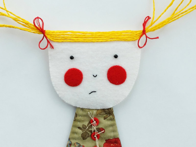 The figure of a sulky girl is made from fabric scraps and felt. She has red cheeks and a grumpy expression. This art doll is made to hang on your wall.