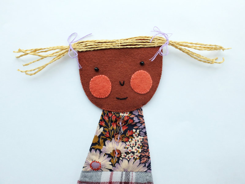 A sweet, little girl with blushing cheeks and a shy expression is handmade from recycled fabrics. She can be hung on your wall.