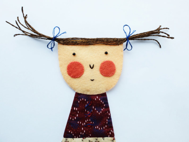 A felt and fabric doll with blushing cheeks and fly-away hair. This art doll is to hang on your wall as a little companion.