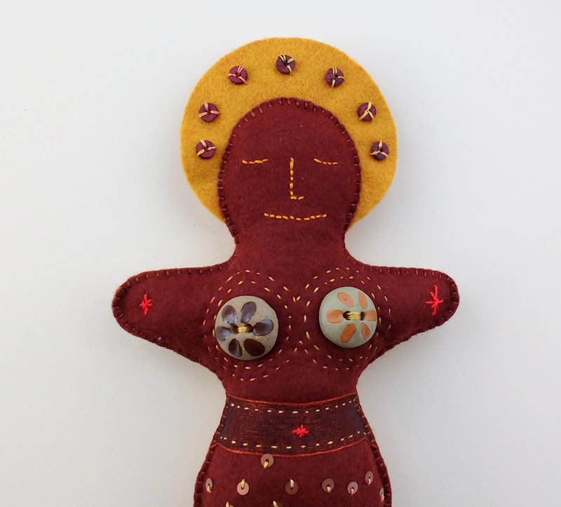 This hand made and hand embellished doll represents the element 'earth'. She has a serene embroidered face with beading, and buttons and bead decoration.