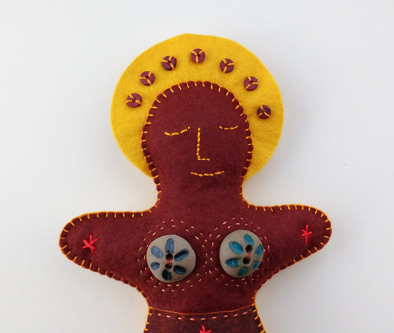 A brown and yellow felt doll representing the element 'earth'. She is decorated with hand stitch, button, bead and sequin embellishment.