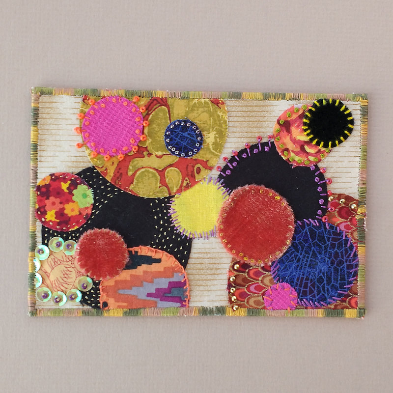 A textile postcard with circles cut from a variety of fabrics, and decorated with hand stitch, beads and sequins.