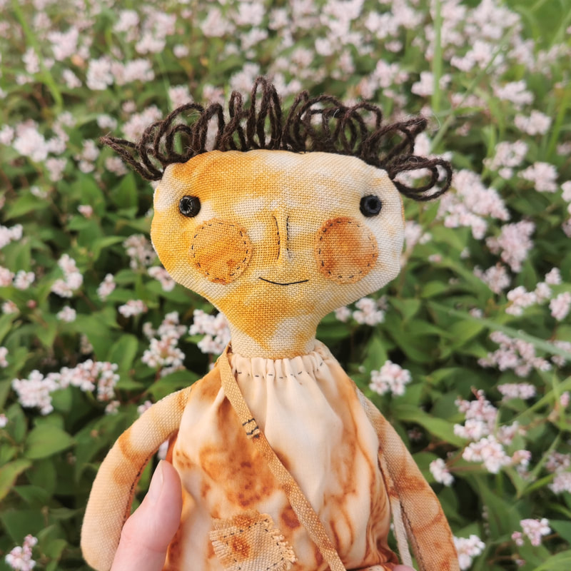 Rusty is a primitive style of doll with wide head and simple features, including glass bead eyes and appliqued cheeks. She is hand sewn from rust-dyed fabrics.