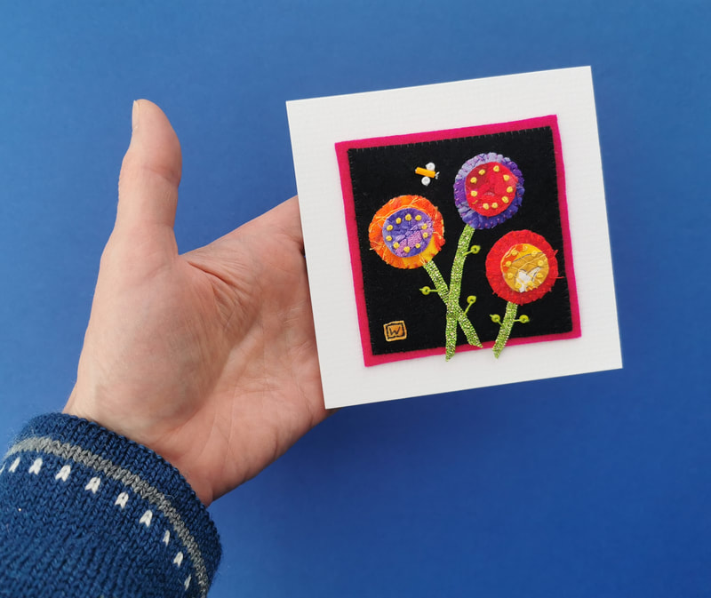 Three colourful flowers are approached by a small insect in this hand sewn small artwork.