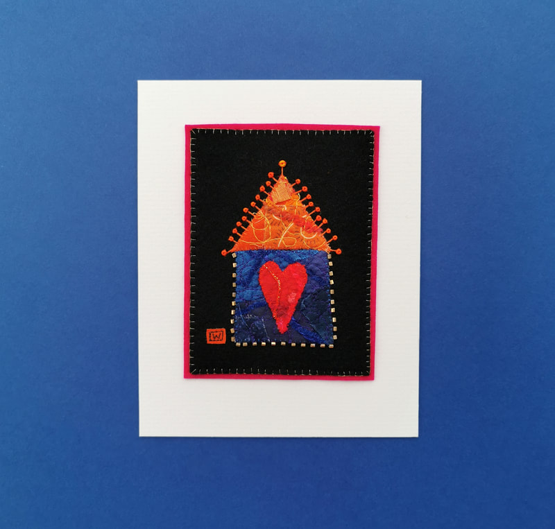 A little blue and orange house contains a big red heart in this piece of textile artwork. This mounted picture is ready to frame, and makes a great gift.