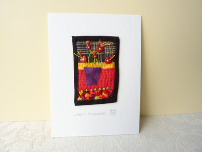 Naif style, hand sewn picture of a vase of red heart flowers, set against a colourful background. The piece is mounted on card, ready to frame or display on a shelf.