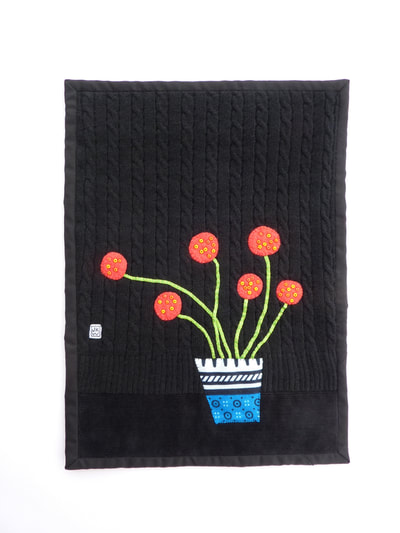 Imaginary red blooms sit against a black, woollen background in this hand sewn applique. Six red flowers with acid green stems extend sinuously from a boldly-patterned flower pot.