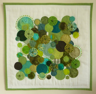 Abstract wall hanging in shades of green circles, representing the abundance of Spring foliage and growth.