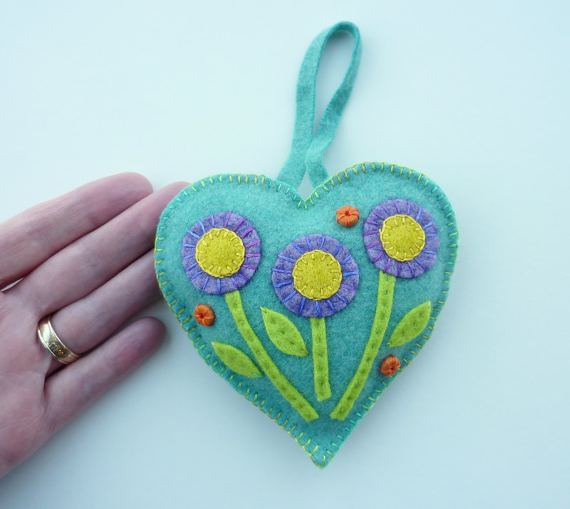 A re-purposed cashmere wool fabric heart with hand-dyed and craft felt flowers appliqued as decoration. Embroidered hand stitch provides a further layer of interest.